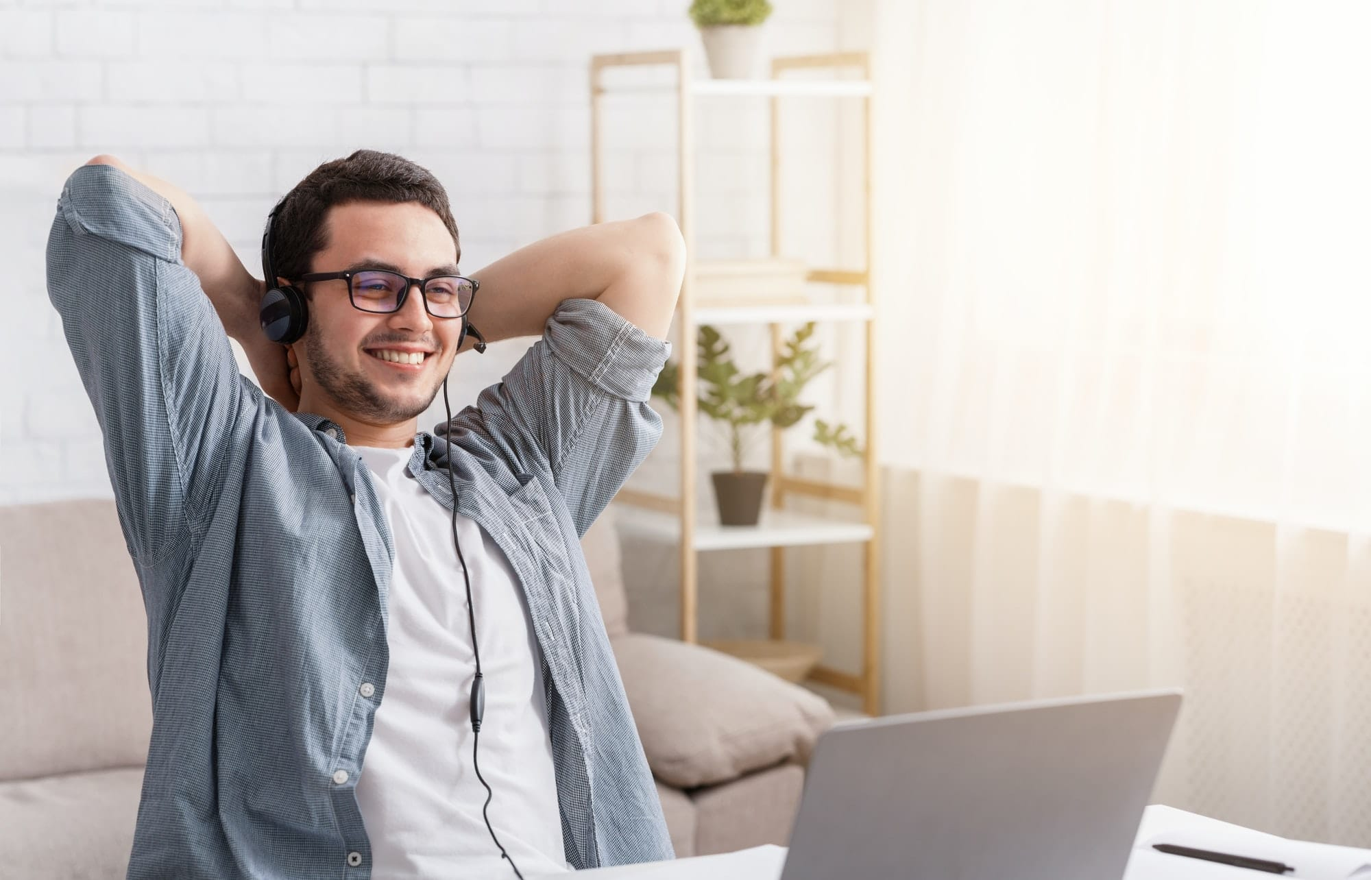 Online webinar and remote work. Man in headset with laptop at home
